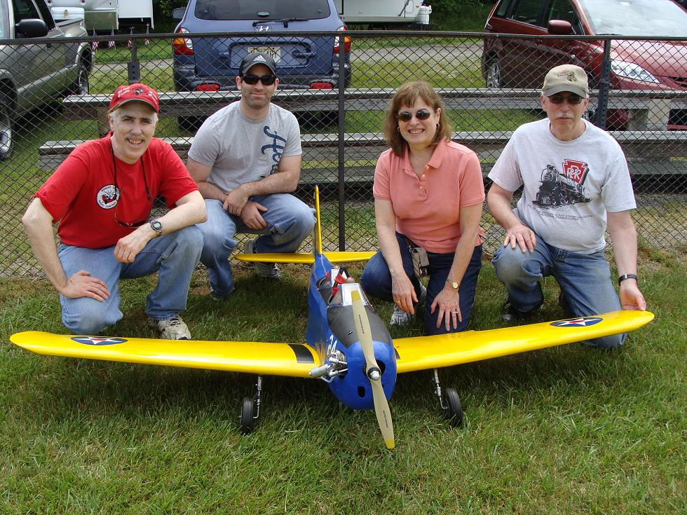 "Carl Gubkin of Monroe, NJ pictured with his nephew, Fiancé Carol and brother, gives good perspective to the wingspan of this 89"" PT-19.  Carl's plane is powered by a Saito 180 and weighs 15 lbs."
