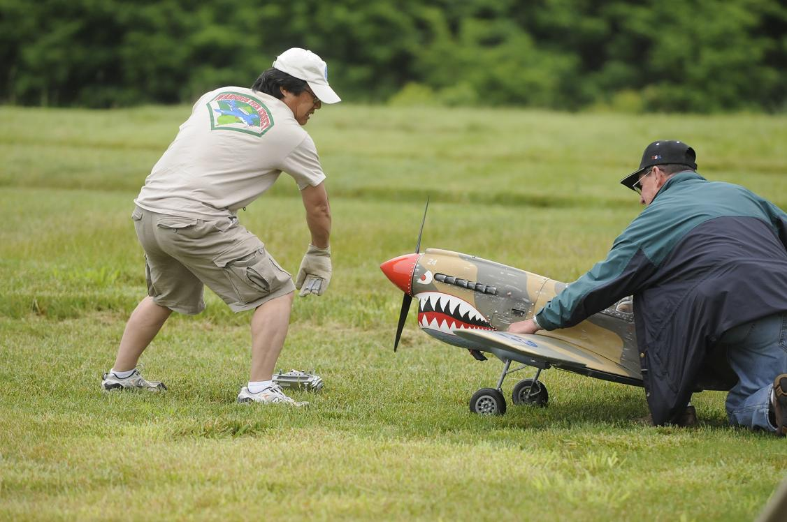 "Nobu Iwasawa starts his 96"" P-40 Warhawk with the assistance of Dan Geerders. This warbird, built by Greg Lucidi, includes retractable landing gear and flaps, weighs 35 lbs., and is powered by a Zenoah G62."